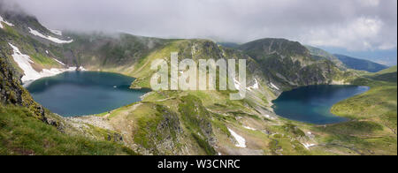 Lots of people hiking, the Eye and The Kidney lake panorama on Rila mountain with single iceberg floating on the glacial lake surface and dramatic fog - Stock Photo