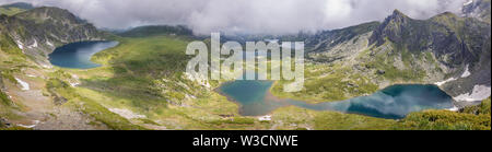 Wide panorama of Rila mountain lakes from a vantage point with dramatic sky, thick mist and smooth, reflective, sapphire blue glacial lakes - Stock Photo