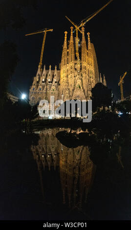 A nighttime view of the Sagrada Familia with a reflection off the water in Barcelona, Spain - Stock Photo