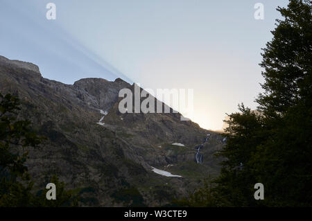 Dusk with sunbeams and Cinca waterfall in Pineta valley in Ordesa y Monte Perdido National Park (Sobrarbe, Huesca, Pyrenees, Aragon, Spain) - Stock Photo