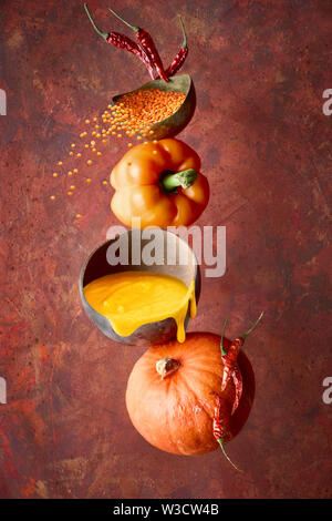 Pumpkin, pepper and orange lentil soup and its ingredients, balance and levitation on dark red background - Stock Photo