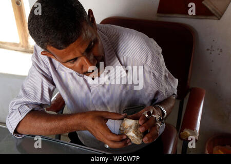 Sanaa, Yemen. 9th July, 2019. Mujahid al-Ansi, a gemstone expert and craftsman, checks a gemstone inside a gemstone manufacturing center in Sanaa, Yemen, on July 9, 2019. The manufacture of agate in Yemen is a centuried handicraft which has been inherited from generation to generation. However, this profession has declined radically because of the war that devastated Yemen's economy and deterred tourists. Credit: Mohammed Mohammed/Xinhua/Alamy Live News - Stock Photo