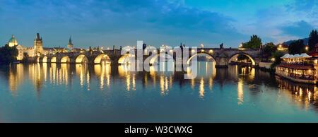 Panoramic image of illuminated Charles bridge in Prague in the evening - Stock Photo