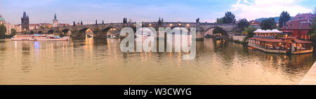 Panoramic image of Charles bridge in Prague early in the evening - Stock Photo