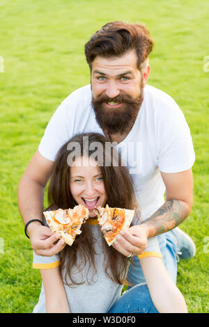 funny time. summer picnic on green grass. Diet. happy couple eating pizza. Healthy food. couple in love dating. hunger. family weekend. fast food. bearded man hipster and pretty woman eat pizza. - Stock Photo