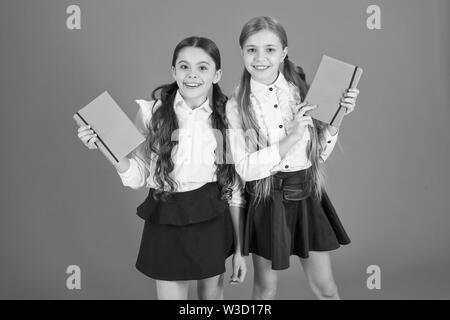 Smart and adorable. Cute schoolgirls holding lesson books. Little children with school diaries for making notes. School children learn reading books. Small girls classmates with workbooks for writing. - Stock Photo