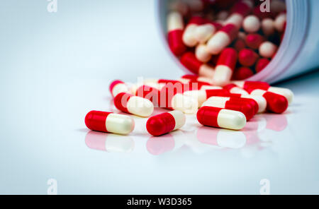 Red-white capsule pills on white table on blurred background of drug bottle. Antibiotics drug resistance. Antimicrobial capsule pills. Pharmaceutical - Stock Photo