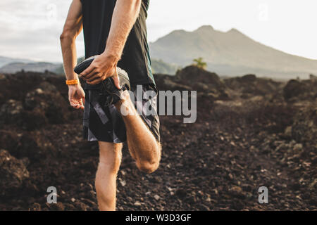 Runner stretching leg and feet and preparing for trail running outdoors. Active and healthy lifestyle concept. Mountain view on background. - Stock Photo