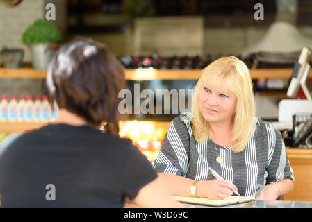 Young depressed woman talking to psychologist during session,mental health.Psychologist with patient in cafe. Portrait of middle aged woman profession - Stock Photo