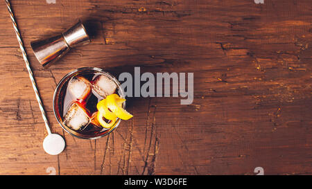 Strong alcoholic drink of brandy whiskey in a glass with ice cubes on a dark wooden background. Top view . Copy space. - Stock Photo