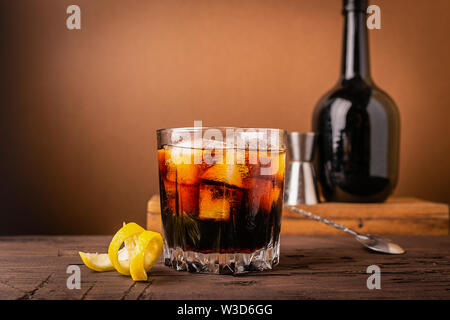 A glass of strong alcoholic drink whiskey brandy a glass glass with ice cubes dark wooden background. Selective focus. - Stock Photo