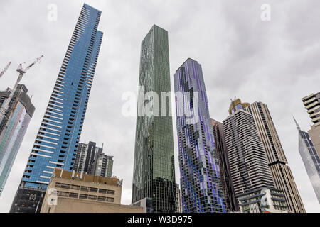 Brightly colored skyscrapers in central Melbourne, Australia, against a cloudy sky - Stock Photo