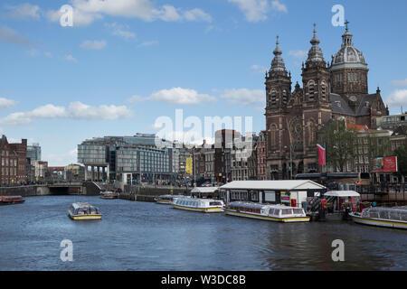 Amsterdam, Holland - June 09, 2019: St. Nicholas Basilica at Prins Hendrikkade near the Oudezijds Kolk water - Stock Photo