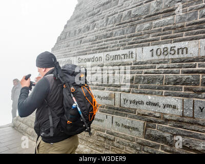 A male climber successfully climbed Mount Snowdon, in the Snowdonia National Park, and takes a photo of the view from the summit - Stock Photo