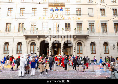 Blumenrain, Basel, Switzerland - March 12th, 2019. Colorful carnival crowd in front of the three kings hotel - Stock Photo