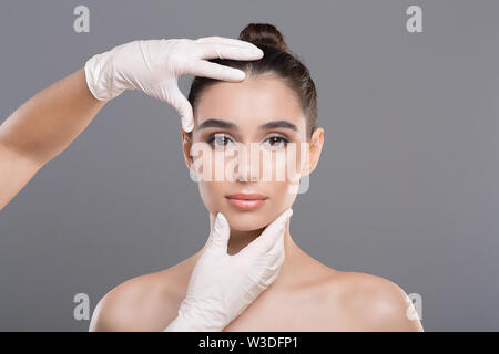 Doctor in gloves touch woman face, gray background - Stock Photo