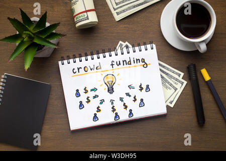 Notepad with crowdfunding concept laying on office table - Stock Photo
