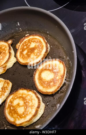 Close-up of making homemade pancakes in a frying pan in the kitchen - Stock Photo