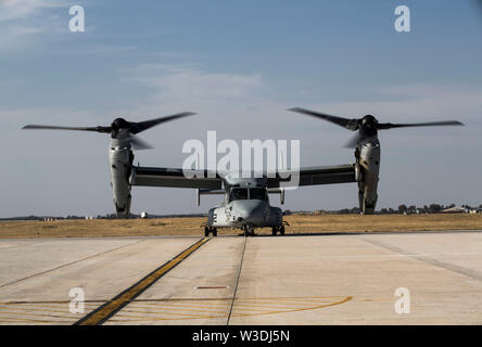 A U.S. Marine Corps MV-22B Osprey with Special Purpose Marine Air-Ground Task Force-Crisis Response-Africa 19.2, Marine Forces Europe and Africa, prepares to conduct an external lift during helicopter support team training on Moron Air Base, Spain, July 9, 2019. The exercise was conducted to increase interoperability between the aviation combat element and logistics combat element. SPMAGTF-CR-AF is deployed to conduct crisis-response and theater-security operations in Africa and promote regional stability by conducting military-to-military training exercises throughout Europe and Africa. (U.S. - Stock Photo