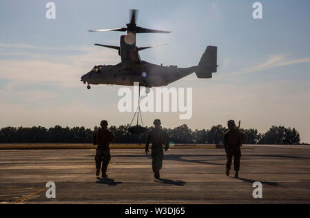 A U.S. Marine Corps MV-22B Osprey with Special Purpose Marine Air-Ground Task Force-Crisis Response-Africa 19.2, Marine Forces Europe and Africa, conducts an external lift during helicopter support team training on Moron Air Base, Spain, July 9, 2019. The exercise was conducted to increase interoperability between the aviation combat element and logistics combat element. SPMAGTF-CR-AF is deployed to conduct crisis-response and theater-security operations in Africa and promote regional stability by conducting military-to-military training exercises throughout Europe and Africa. (U.S. Marine Cor - Stock Photo