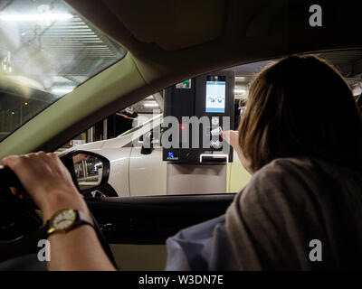 Basel, Switzerland - Jun 5, 2018: Rear view woman inserting ticket in side the barrier ticket machine to exit Basel International Airport parking lot - Stock Photo