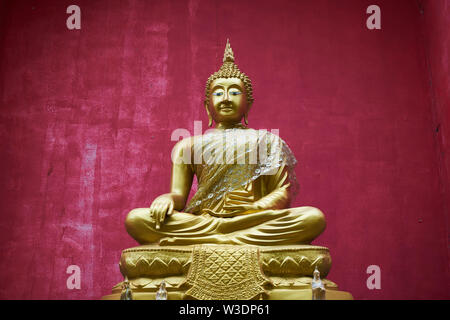 Sitting Buddha in rich red alcove at Wat Buppharam in Chiang Mai, Thailand. - Stock Photo