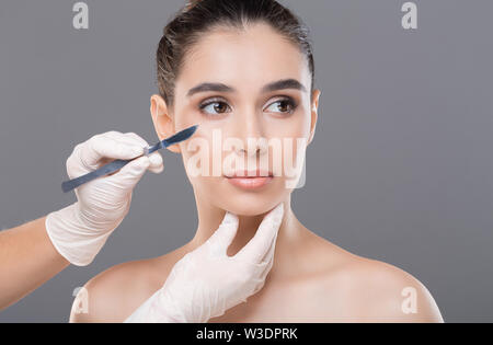 Cosmetologist preparing young woman for plastic surgery procedure - Stock Photo