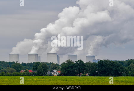 Maust, Germany. 15th July, 2019. Behind residential buildings in the small village of Maust, the steaming cooling towers of the Jänschwalde lignite-fired power plant of Lausitz Energie Kraftwerke AG (LEAG) can be seen. The power plant is the third largest power plant in Germany. It has a capacity of 3000 MegaWatt (MW), of which 2500 MW are in operation. Credit: Patrick Pleul/dpa-Zentralbild/ZB/dpa/Alamy Live News