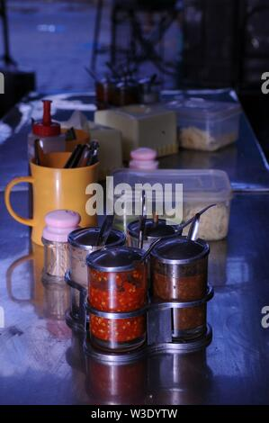 condiments on an open air restaurant table, including chili sauce, at the Russian Market, Phnom Penh, Cambodia. credit: Kraig Lieb - Stock Photo