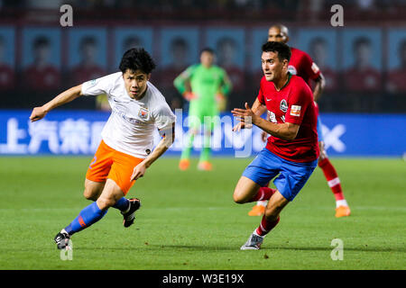 English-born Taiwanese football player Tim Chow, right, of Henan Jianye challenges a player of Shandong Luneng Taishan in their 17th round match during the 2019 Chinese Football Association Super League (CSL) in Zhengzhou city, central China's Henan province, 12 July 2019. Henan Jianye defeated Shandong Luneng Taishan 3-2. - Stock Photo