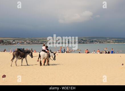 Children Riding Donkeys on Weymouth Beach in July - Stock Photo