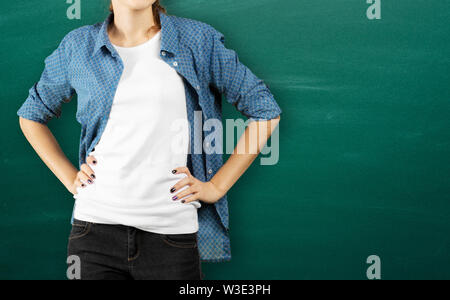 Details of women's clothing. A woman in a blue shirt and blue jeans standing on green background - Stock Photo