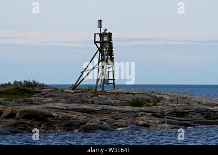 A  sea mark standing on a cliff on the islet of the Bothnian sea - Stock Photo