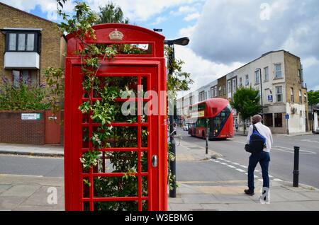iconic red telephone box kiosk in london containing growing bush near archway - Stock Photo