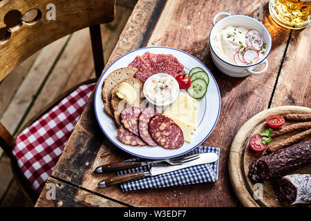 Buffet selection of venison sausages on a wooden board with lunch platter of sliced meat and cheese served with rye bread and salad sides and a mug of - Stock Photo