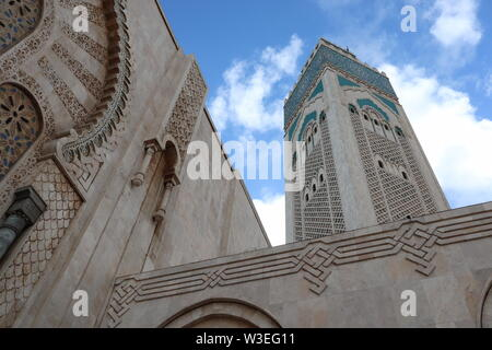 Before entering the Hassan II Mosque, Casablanca, Morocco. Blue Moroccan sky around the world's tallest minaret at 210 metres.