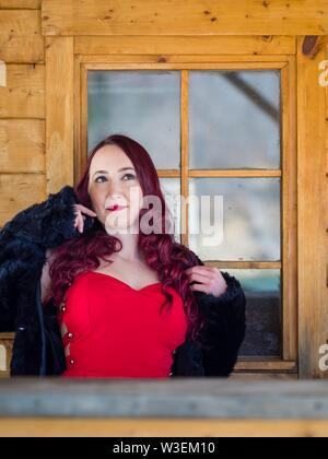 Attractive redhaired female portrait serious looking up upwards away - Stock Photo