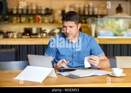 Mature restaurant business owner calculating finance bills of new business – Entrepreneur using tablet and calculator to work and to calculate finance - Stock Photo