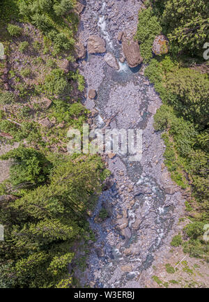 Over head drone view of a glacier melt alpine river valley. - Stock Photo