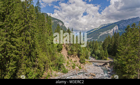 drone view of a alpine river valley and lush green alpine forests surrounded by high mountains. - Stock Photo