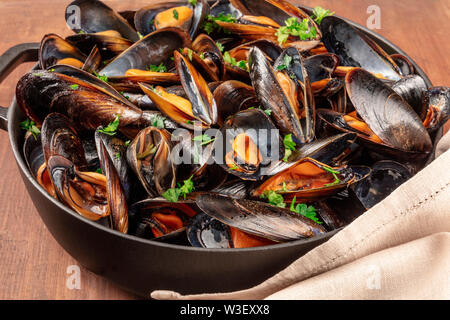 Marinara mussels, moules mariniere, in a large cooking pot, close-up view on a dark rustic wooden background - Stock Photo