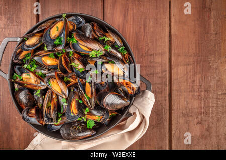 Marinara mussels, moules mariniere, in a cooking pot, overhead view, shot from the top on a dark rustic wooden background with a place for text - Stock Photo