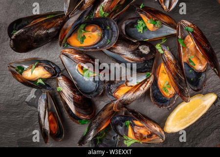Marinara mussels, moules mariniere, with lemon slices, overhead close-up view, shot from the top on a black background - Stock Photo