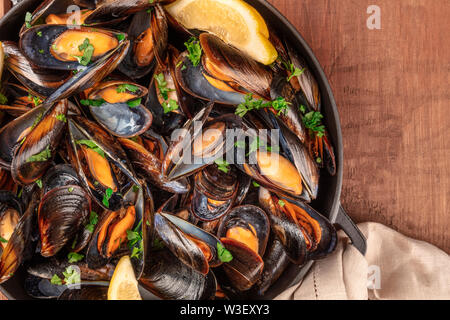 Marinara mussels, moules mariniere, with lemon slices, in a cooking pot, overhead close-up view, shot from the top on a dark rustic wooden background - Stock Photo