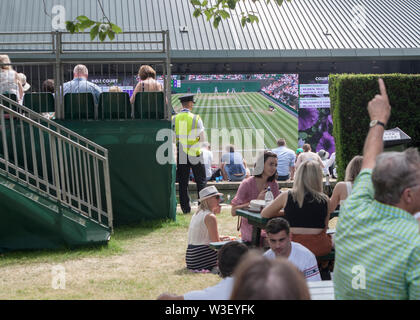 2019 Wimbledon spectators watching big screens from Henman hill / Murray mount ,carp pond foreground - Stock Photo