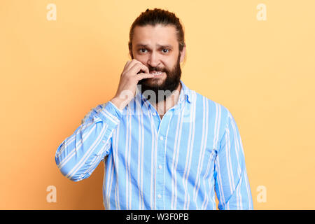 nervous young man with worried expression biting his nails. close up portrait. isolated yellow background. studio shot. - Stock Photo
