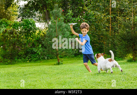 Kid playing with paper airplane and dog outdoors at backyard lawn - Stock Photo