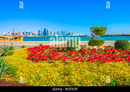 Spring landscape of flower beds and blooming trees on Corniche promenade of Doha Bay in Qatar. Tall skyscrapers of Doha Downtown skyline on distance - Stock Photo