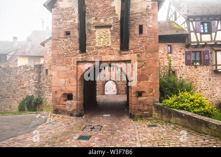 medieval rampart and town gate of village Riquewihr with fog, Alsace, France, touristy village of the Wine Route - Stock Photo