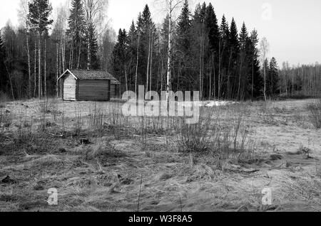 An old small farm house on a field near a forest in black and white.